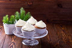 Christmas cupcakes with creamcheese frosting. Homemade christmas cupcakes with creamcheese frosting on cake stand on wooden background with spruce twigs in stock photos