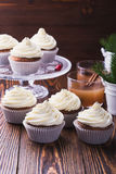 Christmas cupcakes with creamcheese frosting. Homemade christmas cupcakes with creamcheese frosting on wooden background with spruce twigs in ceramic pail and royalty free stock images