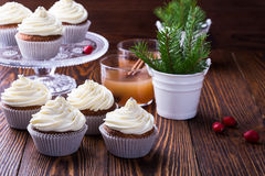 Christmas cupcakes with creamcheese frosting. Homemade christmas cupcakes with creamcheese frosting on wooden background with spruce twigs in ceramic pail and royalty free stock photography