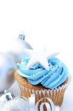 Christmas cupcakes with decorations. Blue icing frosted cup cake with silver christmas ornaments and decorations, plenty of copyspace Stock Photo