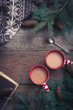 Christmas cups of coffee cocoa with knitted sweater and a book and branche of fir tree Flat lay Top view. Toned Royalty Free Stock Photo