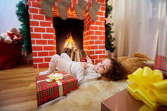 In Christmas curly little girl lying near the fireplace with gif Stock Photo