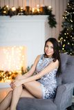 Christmas. Cute girl wearing shiny dress at home sitting on armchair against fireplace and fir tree Stock Photo
