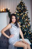 Christmas. Cute girl wearing shiny dress at home sitting on armchair against fireplace and fir tree Royalty Free Stock Image