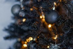 Christmas dark blurred background with a black Christmas tree, ornaments and bokeh lights Royalty Free Stock Photography