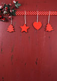 Christmas dark red vintage recycled wood background with hanging wood ornaments. Festive Christmas and Happy Holiday background on dark red vintage recycled wood stock photo