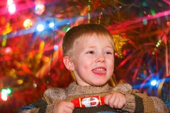Christmas Day. Boy pulling a cracker in front of a  christmas tree Royalty Free Stock Photography