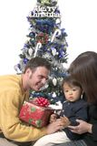 Christmas day 6. Father mother and son under the christmas tree, opening presents Stock Photos