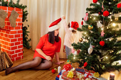 On Christmas Day my mother with a child in the cap of Santa Claus playing near the Christmas tree and fireplace in a happy new ye. Ar stock photo
