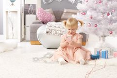 Christmas day. Pretty little girl playing with mobilephone, sitting by christmas tree Royalty Free Stock Image