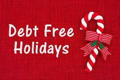 Christmas Debt Free message. Red shiny fabric with a candy cane with text Debt Free Holidays stock image