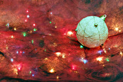 Christmas decor. A creative shot of a white decorative ball on a colorfully decorated background Royalty Free Stock Photo
