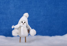 Christmas decor bird in cap on snow stock image