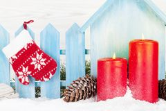 Christmas decor, candles and fir tree. Branch covered by snow in front of wooden wall. Xmas greeting card Royalty Free Stock Images