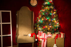 Christmas decor with fir tree and an armchair. Stock Photos