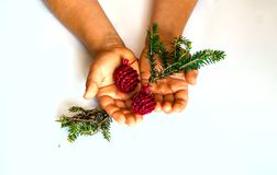 Christmas decor, little hands of child hold in the palm of red balls and spruce branch,concept of New Years holiday, copy space stock photo