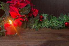 Christmas decor with red candles and poinsettia. On dark wooden table stock photos