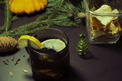 Christmas decor still life. A hot drink with a lemon in a cup, fir tree and branches. Vintage toning Stock Photos