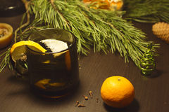 Christmas decor still life. A hot drink with a lemon in a cup, fir tree and branches. Vintage toning Stock Image