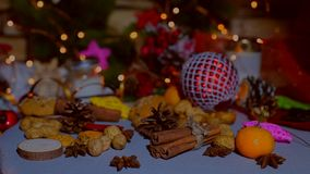 Christmas decor on the table - toys, mandarins, cookies, spices. And the blinking garland stock footage