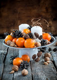 Christmas Decor with Tangerines, Pine cones, Walnuts on Wooden T Royalty Free Stock Photography