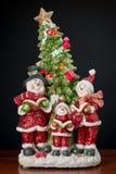 Christmas decor. Three snowman in santa claus dress with tree Stock Image