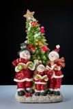 Christmas decor. Three snowman in santa claus dress with tree Stock Photos