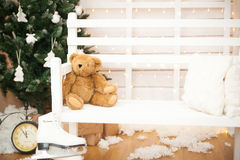 Christmas decor. Christmas tree with gifts, old clock, white bench, holiday lights Stock Photos