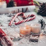 Christmas decor: Warm sweater, cup of hot cocoa with marshmallow, candy, candles and Christmas tree. Winter mood, decoration. stock photo