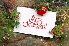 Christmas decor with white paper with an inscription of Merry Christmas Stock Photo