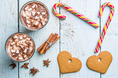 Christmas decor on wooden background with cookies in form heart, cane and two glasses of cocoa. Christmas backgrounds. View from above royalty free stock photo