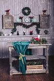 Christmas decor in a wooden house. The shelf is decorated with a garland and fir branches. Wooden table with roses and candles. On velvet fabric Royalty Free Stock Photo