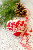 Christmas decoraion greeting card with red heart and cone. On white wooden cracked background copy space Royalty Free Stock Photo