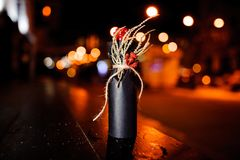 Christmas decorated bottle with ribbon, dried branch and berries in the black paper royalty free stock images