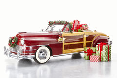 Christmas decorated classic car. Classic woody convertible car decorated for Christmas holiday with bells, garland, wrapped gifts, and festive packages Stock Photography