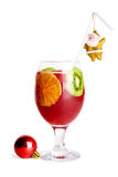 Christmas decorated cocktail. Christmas cocktail decorated with orange and kiwi slices, a straw with a gold Santa Claus and a red glass ball Stock Images