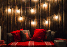 Christmas Decorated Place In A Room With Old Wooden Wall, Lamps, Red Deer Pillows And Plaid Royalty Free Stock Photo