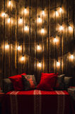 Christmas Decorated Place In A Room With Old Wooden Wall, Lamps, Red Deer Pillows And Plaid Stock Images
