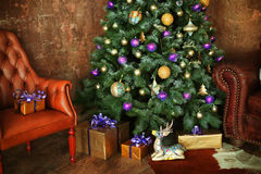 Christmas decorated tree with presents deer and sofa Stock Photos