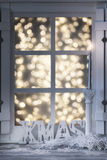 Christmas decorated  window. White window Christmas decorated with the candle light and bokeh lights Royalty Free Stock Photo