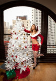 Christmas Decorating pretty woman in Santa Outfit Royalty Free Stock Photos