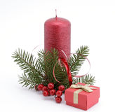 Christmas decoration. Red candle with the twig of the spruce and the gift Stock Photography