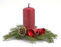 Christmas decoration. Red candle with the twig of the spruce and bells Stock Images