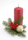 Christmas decoration. Red candle with the twig of the spruce and the nut Stock Image