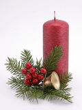 Christmas decoration. Red candle with the twig of the spruce and the bell Royalty Free Stock Photography