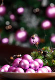 Christmas decoration. Heap of pink balls, blurred Christmas tree on background Stock Photo