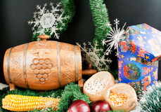 Christmas decoration. With gift box, snowflakes, small keg, garland, onion, corn and haricot beans isolated on black background Royalty Free Stock Photo