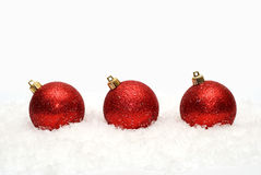 Christmas decoration. Three red Christmas decoration ball on a snowy background Stock Photography