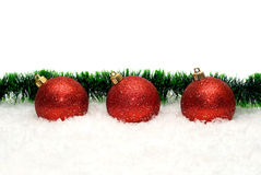 Christmas decoration. Three red Christmas decoration ball on a snowy background Royalty Free Stock Image