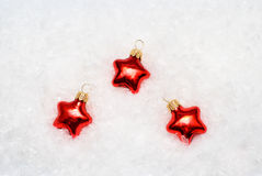 Christmas decoration. Three red Christmas decoration stars on a snowy background Royalty Free Stock Images